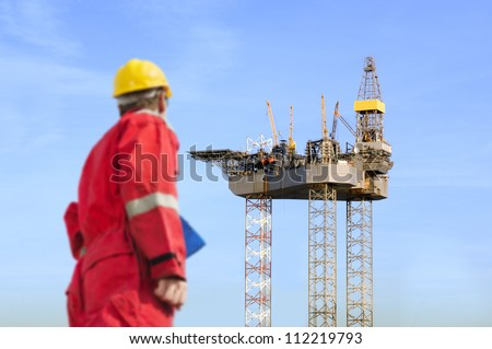 Roughneck (out of focus) looking at a huge oil rig being constructed.