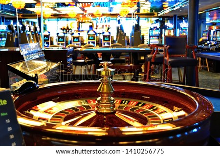 Roulette table in casino with many games and slots in the background. Casino interior, golden equipment and luxury feel. Selective focus. Nobody in the scene