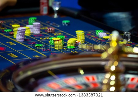 Roulette table with human hands putting down chips in casino. Roulette wheel in the foreground. Gamble game. Unrecognizable people. #1383587021