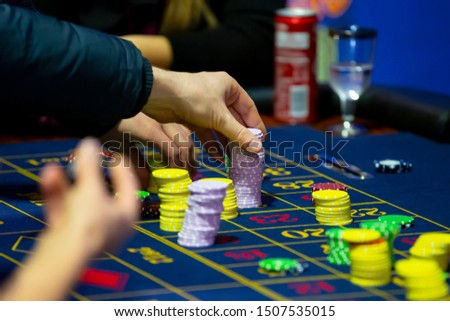 Roulette table with human hands putting down chips in casino. Roulette wheel in the foreground. Gamble game. Unrecognizable people. #1507535015