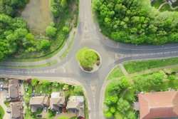 Round a bout on a housing estate in the United Kingdom. No cars driving, with road markings showing cars drive on the left. Houses with parked cars in a area with many trees.