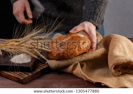 Round artisan bread in the hands of a man close-up. The concept of healthy food and traditional bakery. Rustic.