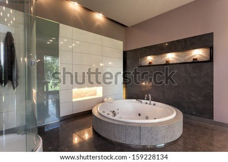Round bath in a luxury tiled bathroom interior