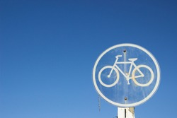Round bicycle sign for bikes lane against the blue sky