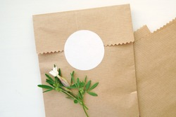 Round blank sticker mockup, circle tag mock up on kraft paper gift bag, adhesive round product label.