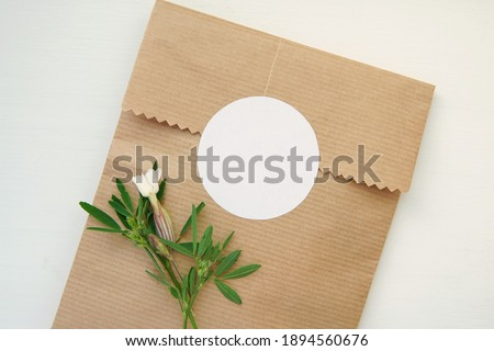 Photo of  Round blank sticker mockup, circle tag mock up on kraft paper gift bag, adhesive thank you card, round product label, pink flowers.