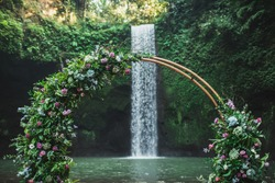 Round bronze wedding arch decorated with pink roses and greens. Unusual location for ceremony near small waterfall in jungle. Tibumana, Bali, Ubud.