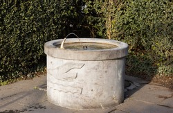 round brown stone fountain with engraved seagull and wavy water, the water tap is in operation, by day, without people