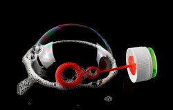 Round bubble wand, toy for children with colorful bubble isolated on black background, top view