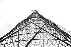 Round building construction. Abstract modern building. Architectural background. Telecommunication, TV, radio antenna tower, high voltage line, metal tower.