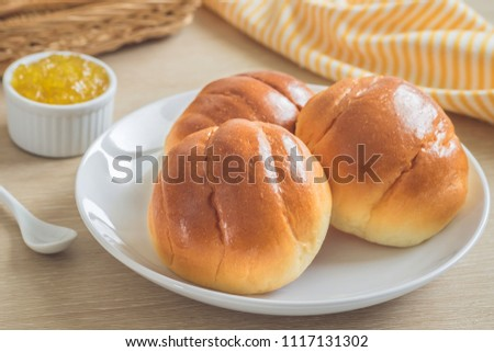 Round bun, bread rolls on white plate and pineapple jam
