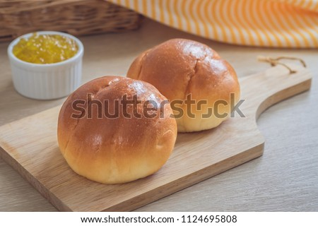 Round bun, bread rolls on wooden plate and pineapple jam