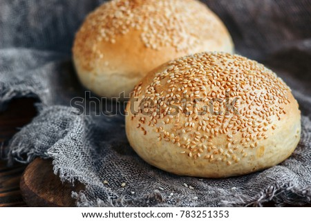 Round bun, sesame bun, bread rolls. Tasty burger bread with sesame on wooden, burlap background. Freshly baked hamburger buns. Top view.