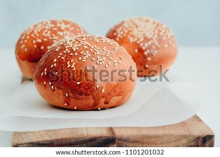 Round bun, sesame bun, bread rolls. Tasty burger bread with sesame on wooden. Freshly baked hamburger buns.