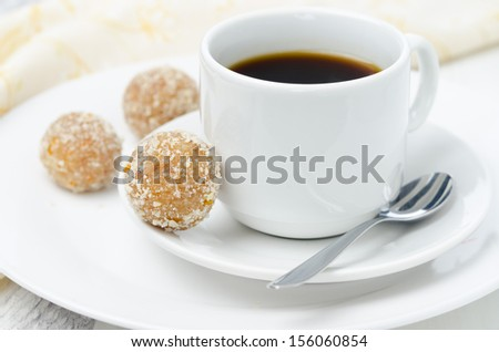 round candy made of almonds, ginger and dates and cup of coffee