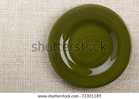 Round ceramic dish on a background mat for the second course.