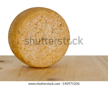 Round cheese aka wheel, truckle on board, white background