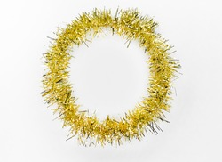Round circle of yellow, golden tinsel on a white background. Christmas decorations. New year concept