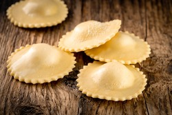 Round classic ravioli with filling on a wooden background. Fresh Italian pasta ravioli, rustic style