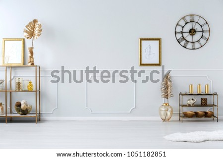 Round clock and poster on white wall with copy space in sophisticated living room interior #1051182851