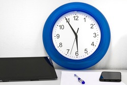 round clock on the table. five minutes before the end of the working day. five minutes to six. end of the working day.