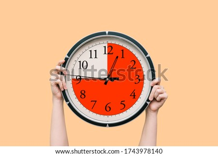 Round clock with a dial shows three-quarters of an hour. The time timer is fifteen minutes. Watch in the hands of a woman. The concept of a schedule, and assignment of time to complete work Stock photo ©