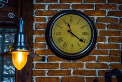 Round clock with Roman numerals hang on a brick wall
