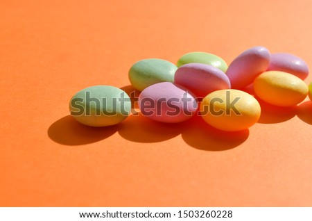 Round colored candies lie in bunch on orange color, with copyspace on sunshine, closeup, closeup