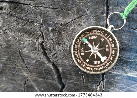 round compass on blue wooden background as symbol of tourism with compass, travel with compass and outdoor activities with compass