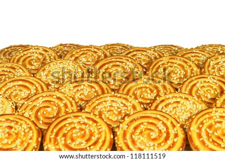 Round cookies with sesame seeds laid out in rows on a white background