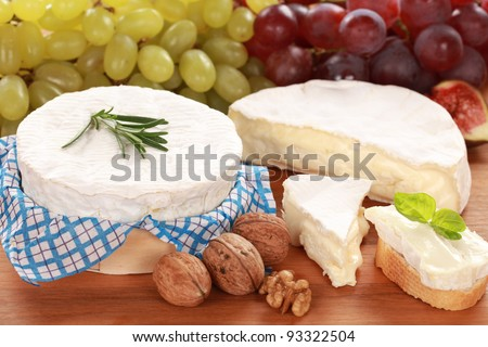 Round creamy soft camembert cheese served with grapes and walnuts - stock photo