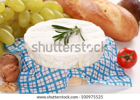 Round creamy soft camembert cheese served with walnuts and grapes