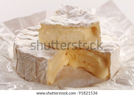 Round creamy soft camembert cheese, with a wedge cut out