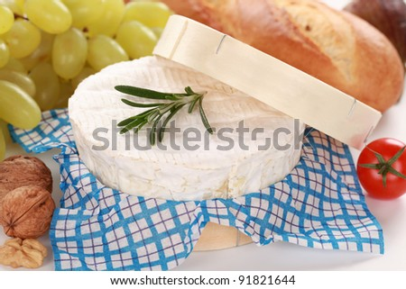 Round creamy soft camembert cheese with grapes, baguette and nuts