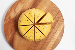 Round cumin cheese sliced into eight pieces. Traditional latvian cumin cheese used in John's day and Ligo celebration