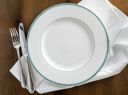 Round dinner plate with knive and fork on white napkin and wooden table flat lay