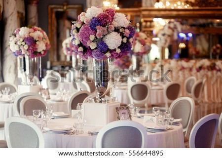 Round dinner table decorated with pink and violet hydrangeas stands in luxurious restaurant Сток-фото ©