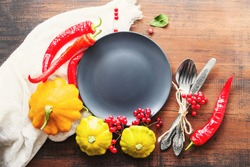 Round empty gray plate with space for text, yellow squash, red hot peppers, viburnum berries and cutlery on an old wooden surface, top view. Autumn or Thanksgiving background.