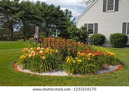 Round flower garden on side of home surrounded by daylillies.