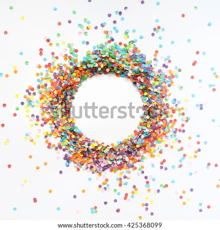 Round frame made of colored confetti. White background. Festive confetti. #425368099