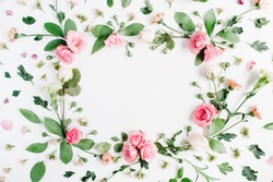 Round frame made of pink and beige roses, green leaves, branches, floral pattern on white background. Flat lay, top view. Valentine's background
