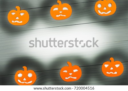 Round frame with different pumpkin paper silhouettes on a gray wooden table. Halloween celebration. Copy space for greetings #720004516