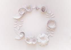 Round frame with white paper flowers on white background. Cut from paper.