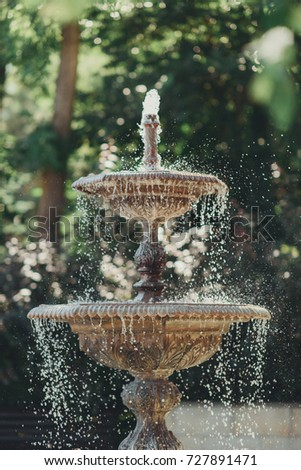 Round garden water fountain tiered in the park. Outdoor romantic cities beautiful fountain background.
