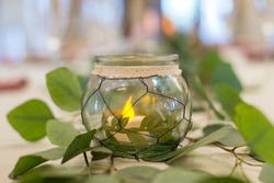 Round glass candle centerpiece with green leaves decor at weddid