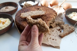 Round gluten-free homemade bread from buckwheat, chickpea, rice, cornmeal, eggs and honey. Healthy eating concept, flat lay. A piece of bread in a female hand.