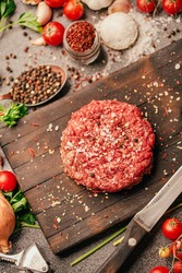 Round ground beef portioned beef patty made from beef mince on a wooden board. Hamburger meat seasoned and ready for a barbecue.Spices and condiments for a grill.Homemade burger recipe.Prepared burger