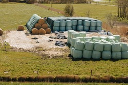 Round hay bales packed in plastic. Bales of straw on a farm in Germany.