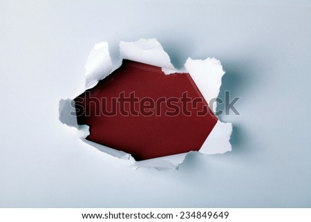 Round hole in paper with red background inside