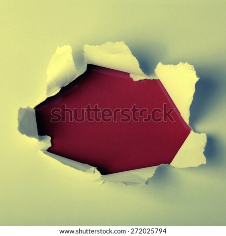 Round hole in paper with red background inside. Square toned image, instagram effect